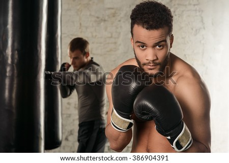 Dark-skinned guy with naked torso in boxing gloves, boxing in the loft gym, boxing guy, black punching bags in the background - stock photo