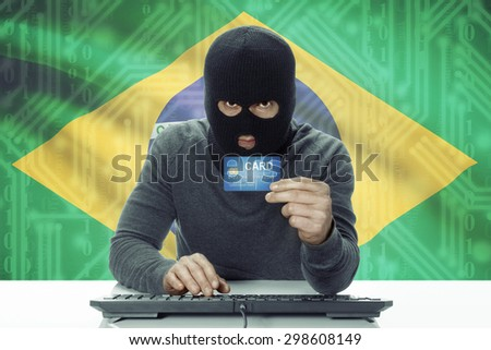 Dark-skinned hacker with credit card and flag on background - Brazil - stock photo