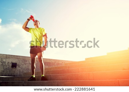 Dark-skinned runner drink water after intensive evening run, beautiful fit man in bright fluorescent sportswear, sports fitness concept - stock photo