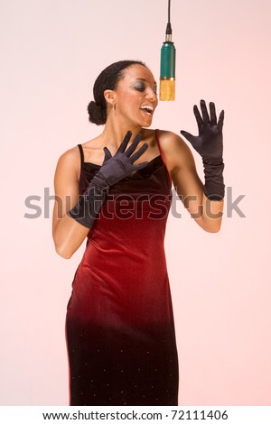 dark skinned sexy female in red concert dress and black gloves sings by microphone - stock photo
