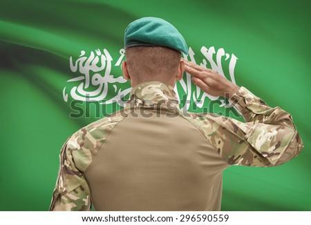 Dark-skinned soldier in hat facing national flag series - Saudi Arabia - stock photo