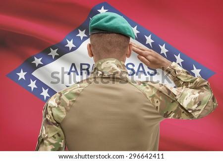 Dark-skinned soldier in hat facing US state flag series - Arkansas - stock photo