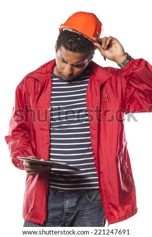 dark-skinned worker with helmet and notepad looking concerned - stock photo