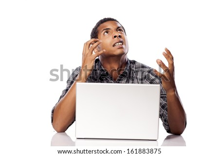 dark-skinned young man desperate and helpless gesture with his laptop - stock photo