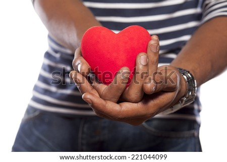 dark-skinned young man holding an object in heart shape in his hands