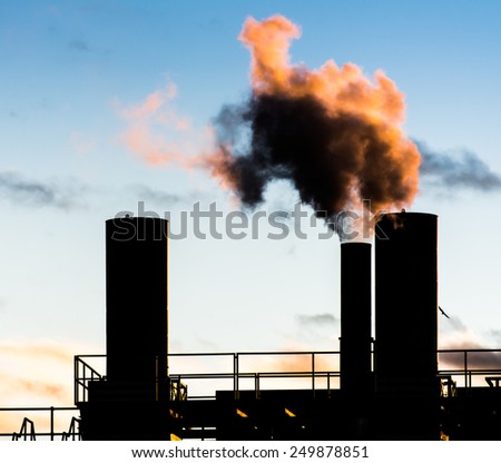 Dark smoke comming from the chimneys of an old factory. - stock photo