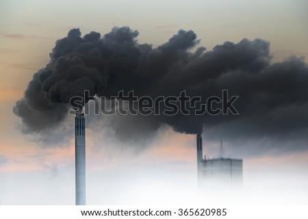 Dark smoke from chimneys of power plant on orange sky - stock photo