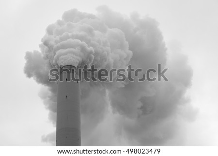 Dark smoke is streaming out of a chimney on a coal power station