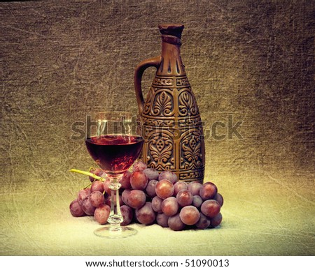 Dark Still Life - a clay bottle, glass and grapes - stock photo