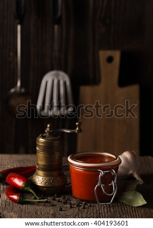 Dark still life with chili pepper hot sauce and ingredients - stock photo