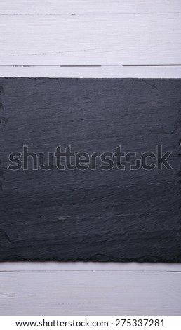 dark stone plate on wooden background - stock photo