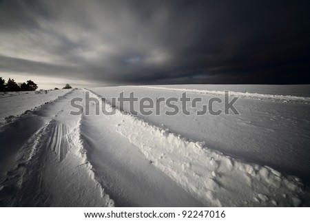 Dark storm clouds and winter road in a field - stock photo