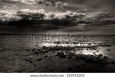 Dark storm clouds gathering over a rocky beach near Homer, Alaska overlooking the Kachemak Bay in black and white.