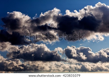 Dark storm clouds on blue sky before rain - stock photo