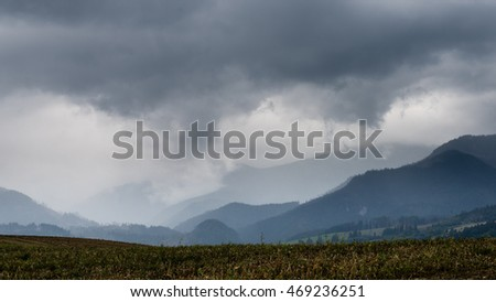 Dark storm clouds over meadow with green grass and mountains in background