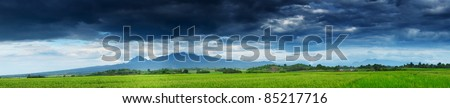 Dark storm clouds over mountains and green rice fields with small wooden buildings