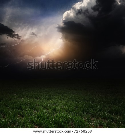 Dark storm clouds with flashes over meadow with green grass - stock photo