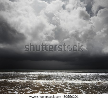 Dark storm rainy clouds over tropical sea with waves