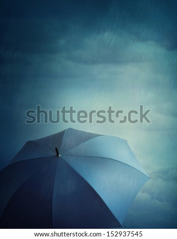 Dark stormy clouds and umbrella - stock photo