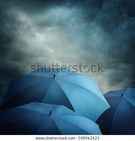 Dark stormy clouds and umbrellas - stock photo