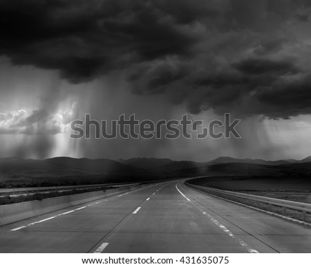 Dark stormy clouds on road