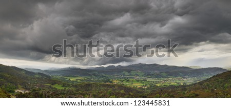 Dark stormy clouds over a green valley in Cantabria Spain