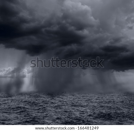 Dark stormy clouds over the ocean - stock photo