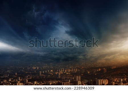 Dark stormy clouds over town, stormy weather, powerful rainstorm hits town - stock photo