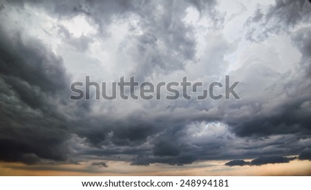 Dark stormy sky with light breaks in the clouds. - stock photo