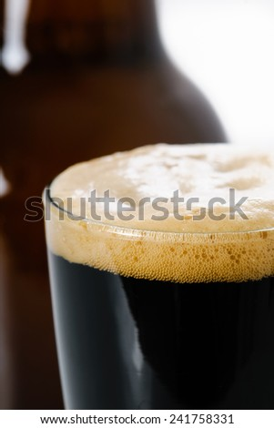 Dark Stout beer with bottle on white - stock photo