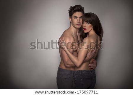 Dark studio portrait with vignetting of a passionate sexy topless couple indulging in romantic foreplay in a close embrace - stock photo