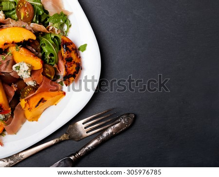 Dark style photo of delicious salad with grilled peaches and prosciutto, top view - stock photo