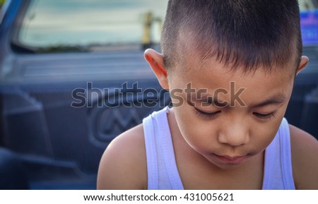 Dark Tone Child making a sad face getting in trouble. Sadness Face portrait.cute young Asian boy - stock photo