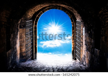 Dark tunnel corridor with arch opening to the sun. Light at the end of the tunnel. - stock photo