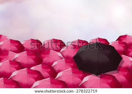 dark umbrella over many red ones. - stock photo