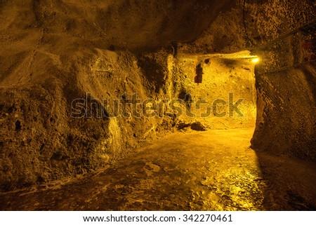 Dark underground corridor in a dungeon with light at exit - stock photo