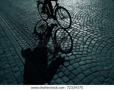 Dark urban cyclist  on his way home after work - Denmark. - stock photo