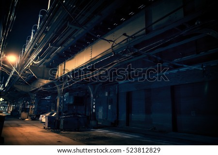 Dark urban downtown city alley at night with garbage trash bins, car garage doors and elevated train tracks