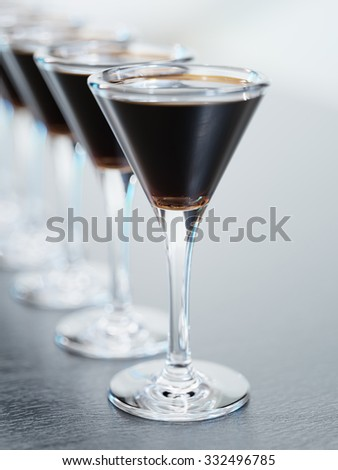 Dark vine or cocktail glasses standing in a row closeup - stock photo