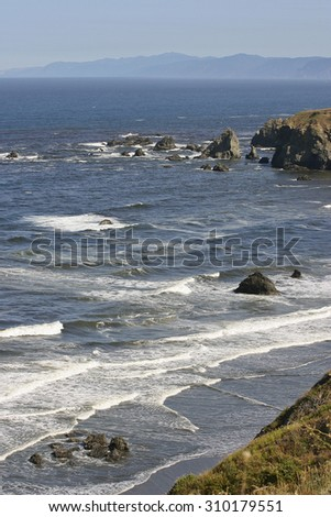 Dark volcanic rock litters the beach and ocean on the coast of the western United States of America - stock photo