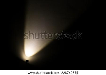 Dark Wall Illuminated from the Left Corner Spotlight Lamp, black background - stock photo