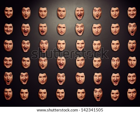 dark wall with different emotional masks - stock photo