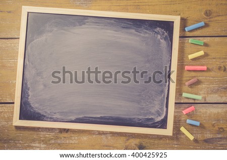Dark wiped chalkboard on wooden background