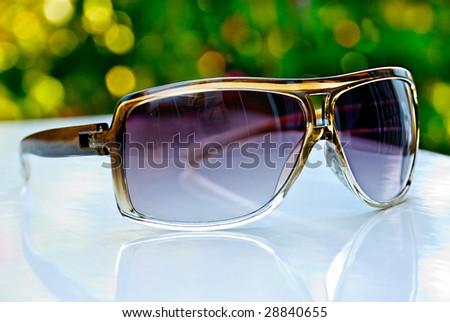 Dark women's sunglasses isolated on a white desk - stock photo