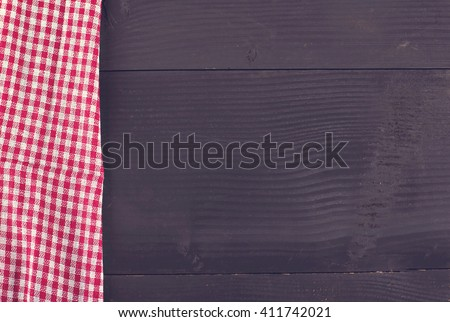 dark wood background and red checkered napkin - stock photo