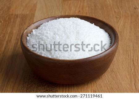 Dark wood bowl of dessicated coconut on wood table. - stock photo
