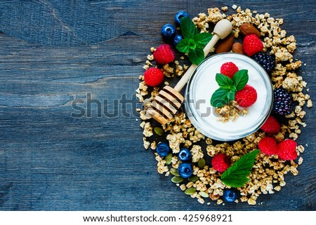 Dark wooden background with ingredients for healthy breakfast - granola, berries, nuts. Top view composing with space for text. Flat lay. Healthy food, Diet, Detox, Clean Eating or Vegetarian concept. - stock photo
