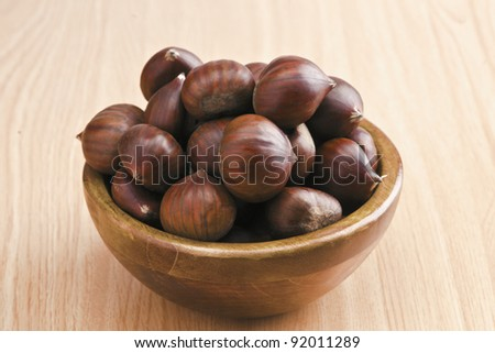 dark wooden bowl with chestnuts. wood-based - stock photo