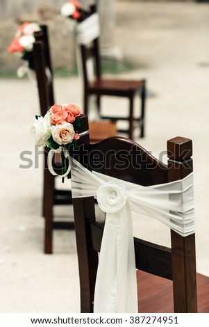 Dark wooden chairs with floral and fabric decor outdoors