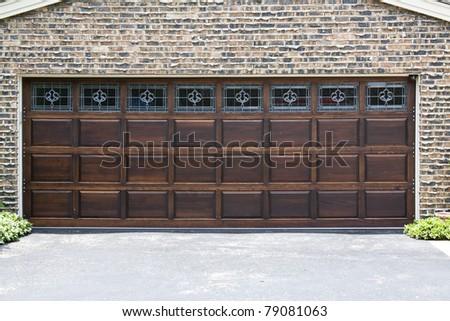 Dark Wooden Garage Door with brick wall background - stock photo